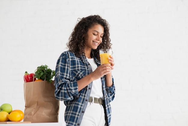 Mujer afroamericana sentada junto a una bolsa de verduras