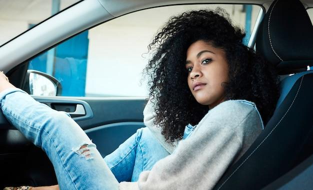 Mujer afroamericana sentada posando dentro de su coche mono vaquero