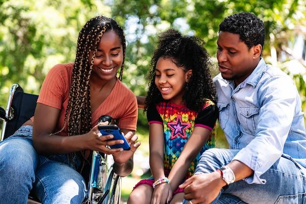 Una mujer afroamericana en silla de ruedas disfrutando de un día en el parque con su familia mientras usa un teléfono móvil juntos