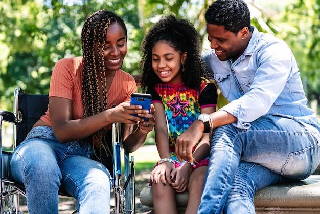 Una mujer afroamericana en silla de ruedas disfrutando de un día en el parque con su familia mientras usa un teléfono móvil juntos.