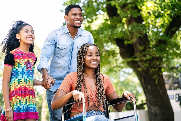 Una mujer afroamericana en silla de ruedas disfrutando de un paseo al aire libre con su hija y su marido.