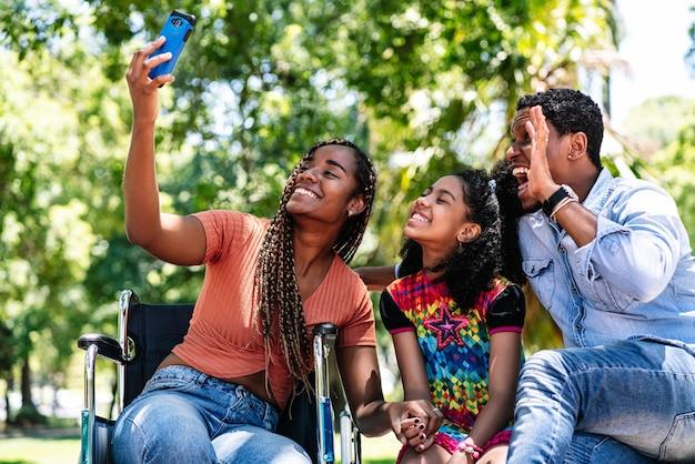 Una mujer afroamericana en silla de ruedas tomando un selfie con su familia con un teléfono móvil mientras disfruta de un día en el parque.