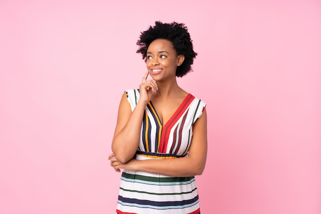Mujer afroamericana sobre pared rosa