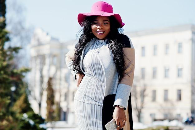 Mujer afroamericana en sombrero y abrigo con teléfono caminando en las calles.