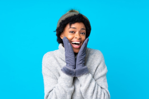 Mujer afroamericana con sombrero de invierno sobre pared azul