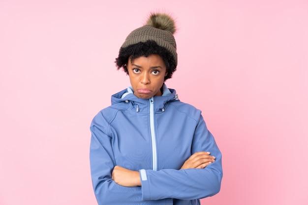 Mujer afroamericana con sombrero de invierno sobre pared rosa aislado
