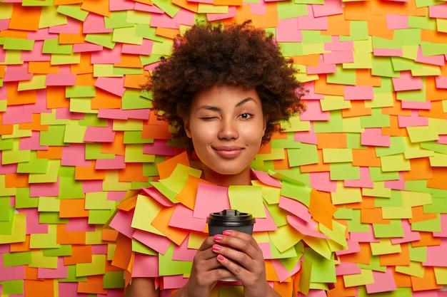 Mujer afroamericana soñolienta guiña un ojo, sostiene una taza de café desechable, trabaja durante muchas horas, trata de estar fresca, tiene el cabello rizado natural, pega la cabeza a través del fondo de papel, notas adhesivas alrededor