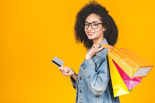 Mujer afroamericana sonriente y alegre con coloridas bolsas de compras y tarjeta de crédito