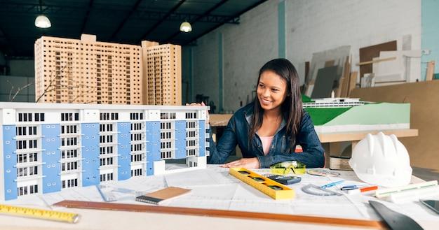 Mujer afroamericana sonriente cerca del modelo de construcción en mesa con equipos