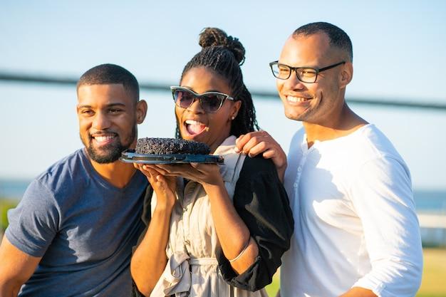 Mujer afroamericana sonriente que sostiene la torta de chocolate. jóvenes felices posando juntos. celebración de fiestas de cumpleaños