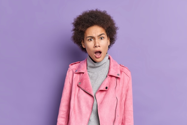Mujer afroamericana sorprendida con cabello rizado y tupido parece indignada, ha abierto la boca ampliamente