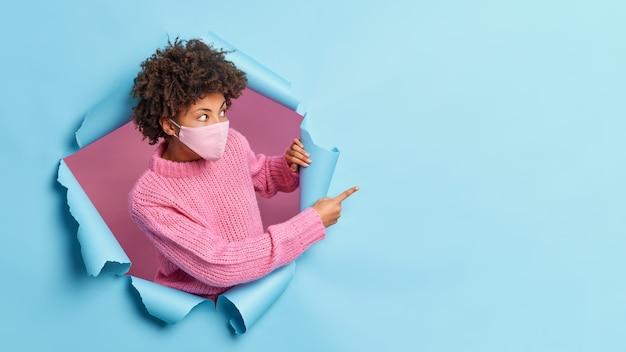 Mujer afroamericana sorprendida se para de lado y apunta hacia un espacio vacío