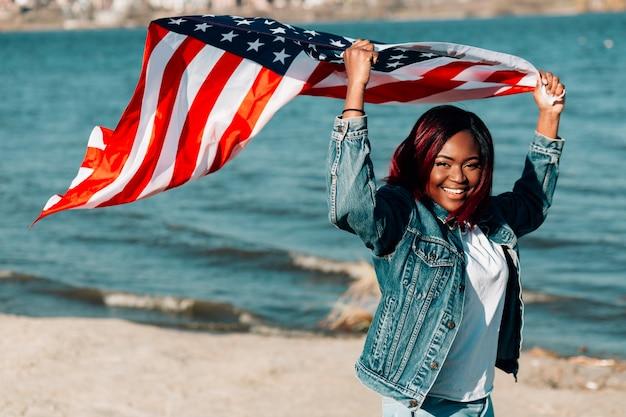Mujer afroamericana sosteniendo la bandera estadounidense ondeando en el viento