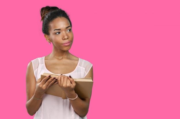 Mujer afroamericana sosteniendo una pila de libros