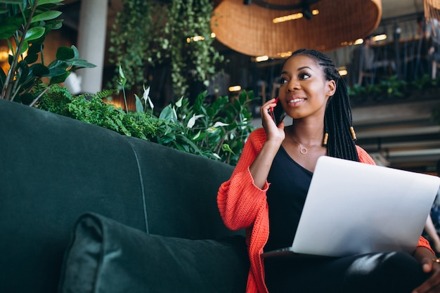 Mujer afroamericana con teléfono y computadora portátil en un café