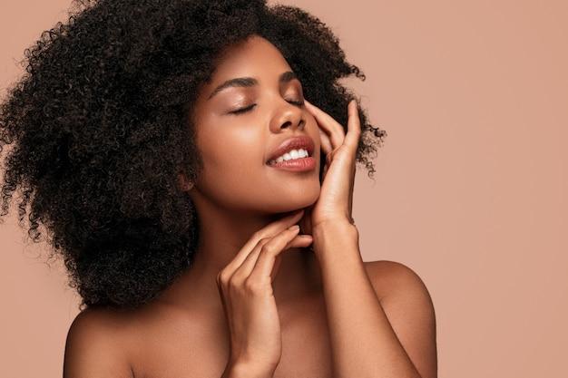 Mujer afroamericana tocando la piel limpia