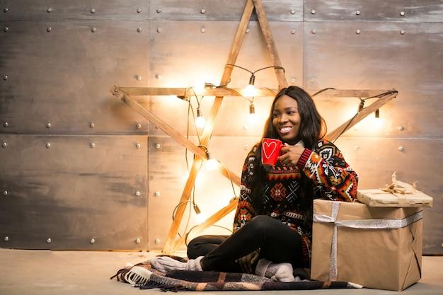 Mujer afroamericana tomando café en una víspera de navidad