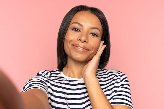 Mujer afroamericana tomar una foto selfie en el teléfono inteligente después del tratamiento de spa de piel toque la cara perfecta