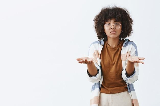 Mujer afroamericana triste y sombría desesperada con gafas transparentes con el pelo rizado levantando las palmas cerca del pecho en un gesto confuso y desorientado, no puedo entender por qué