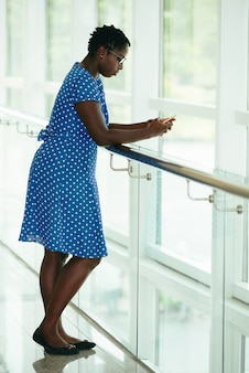 Mujer afroamericana en vestido de lunares apoyándose en la barandilla en el balcón y usando un teléfono inteligente