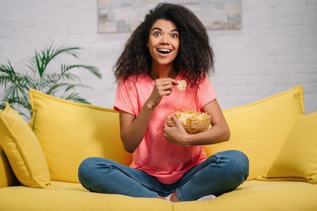 Mujer afroamericana viendo películas, relajarse en casa