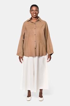 Mujer afroamericana vistiendo camisa marrón de manga larga con pantalón culotte blanco