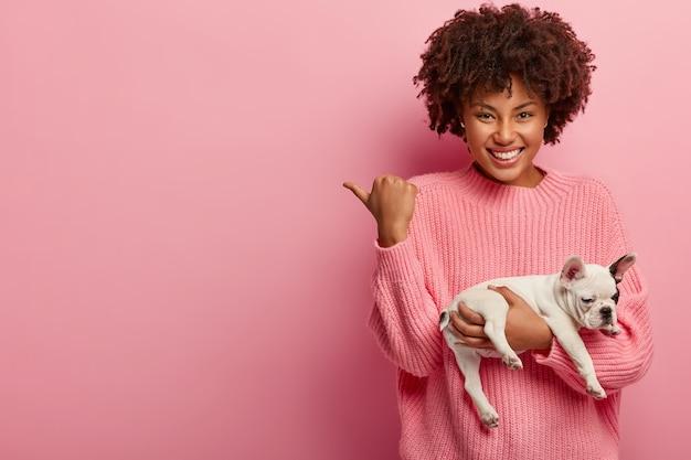 Mujer afroamericana vistiendo suéter rosa con cachorro