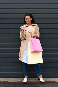 Mujer afuera mirando smartphone y sosteniendo bolsas de compras