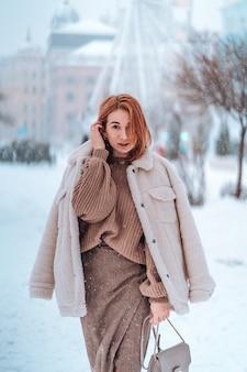 Mujer afuera en nevando día frío de invierno