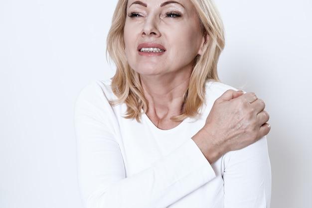 Una mujer agarrada a su hombro que duele.