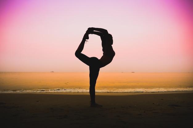 Mujer agarrando una pierna por la espalda en una playa