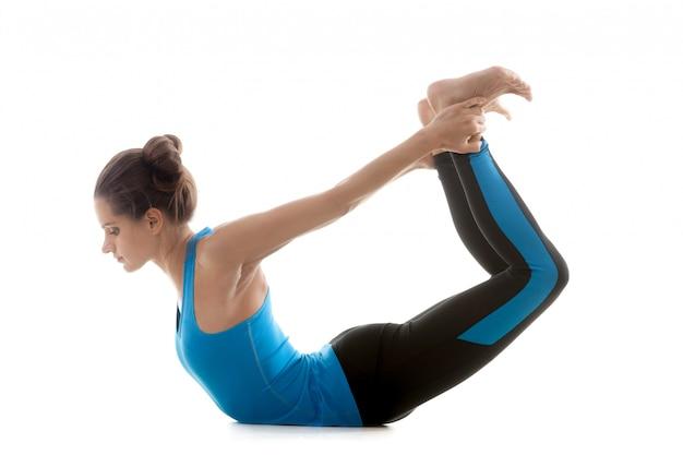 Mujer agarrando sus pies desde la espalda