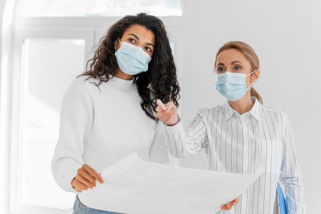 Mujer y agente de bienes raíces con planes de casa juntos con máscaras médicas