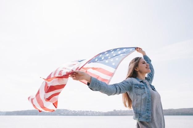 Mujer agitando gran bandera de estados unidos