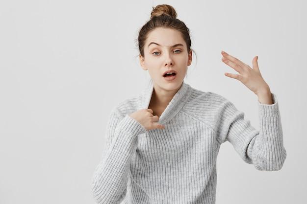 Mujer agotada gesticulando con la mano caliente quitándose el suéter. compradora femenina siente calor haciendo cola mientras realiza compras en el centro comercial. lenguaje corporal
