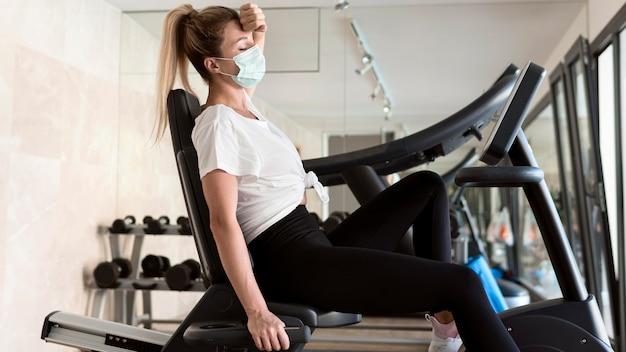 Mujer agotada con máscara médica en el gimnasio