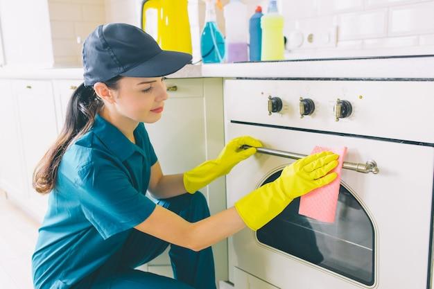 Mujer agradable y alegre se sienta en posición de escuadrón en la estufa y limpia la puerta
