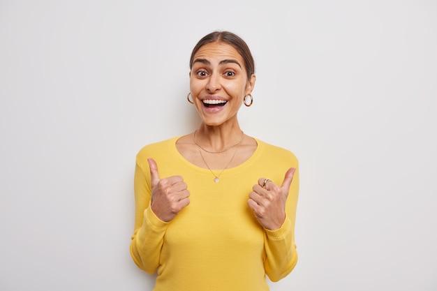 Una mujer agradable y complacida muestra el pulgar hacia arriba y muestra una retroalimentación positiva, como un gesto que demuestra que la aprobación usa un puente amarillo informal aislado sobre una pared gris que lo alienta