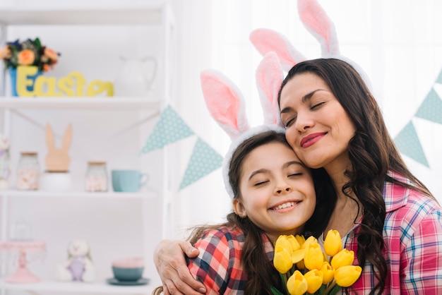 Mujer agradable y su hija abrazándose el día de pascua