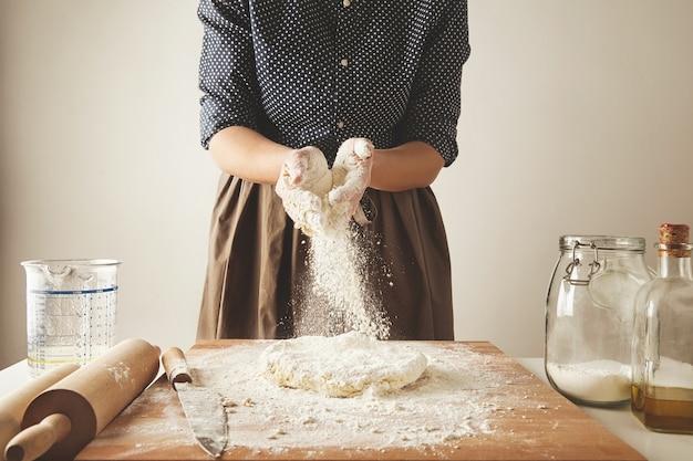 La mujer agrega un poco de harina a la masa en la mesa de madera cerca del cuchillo, dos rodillos, taza de medida, jae transparente con harina y botella de aceite de oliva. guía paso a paso de albóndigas de pasta para cocinar
