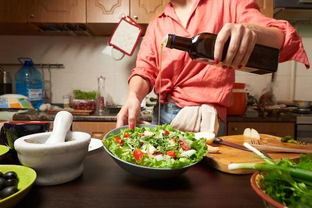 Mujer agregando aceite de oliva en saludable ensalada griega