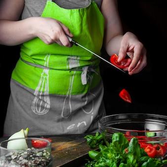 Mujer agregando tomate en ensalada con pepinos y vista lateral de espinacas