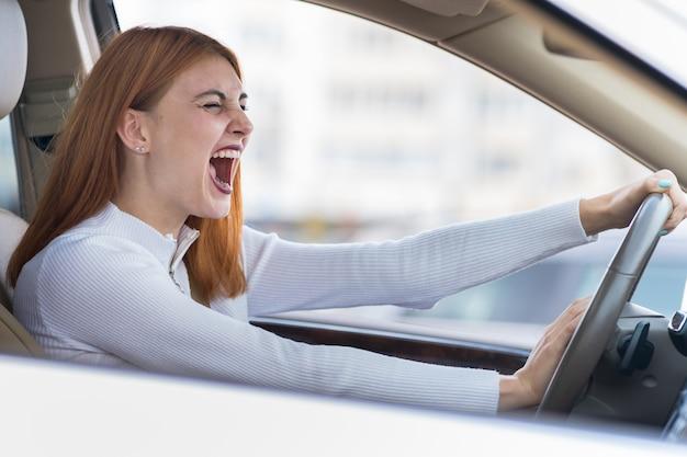 Mujer agresiva enojada conduciendo un automóvil gritándole a alguien