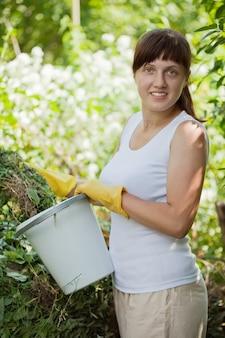 Mujer agricultor de compostaje de hierba