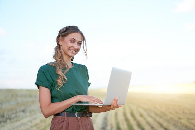 Mujer agricultora agricultura inteligente tierras de cultivo permanente sonriendo con portátil