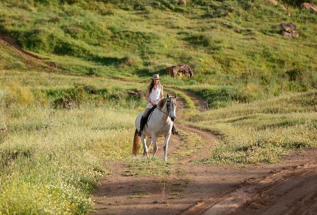 Mujer agricultora paseos a caballo en la naturaleza