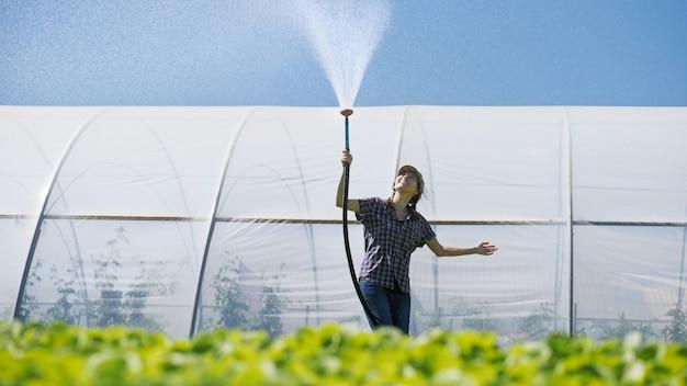 Mujer agricultora regando plántulas verdes en el campo cerca del invernadero.