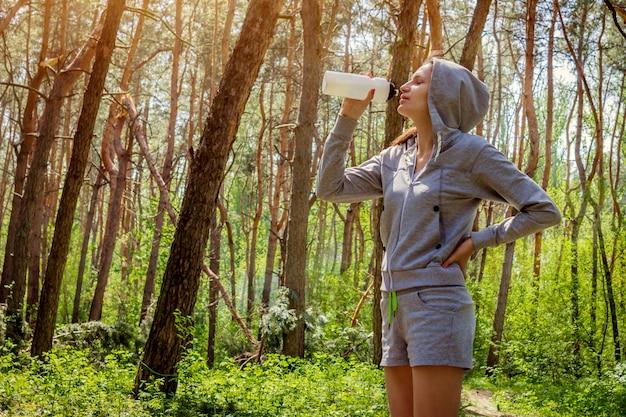 Mujer agua potable después de correr en el bosque
