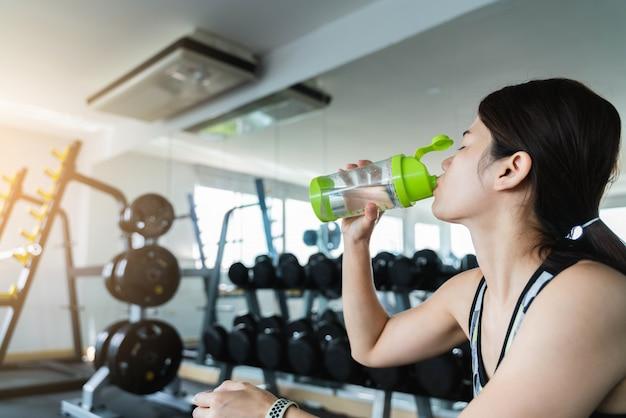Mujer, agua potable, en, gimnasio, después, entrenamiento