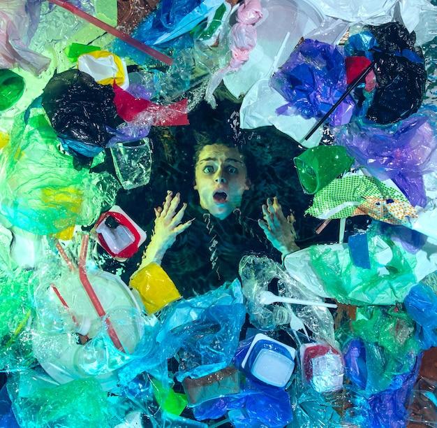 Mujer ahogándose en agua debajo de la pila de recipientes de plástico, basura. botellas y paquetes usados llenando el océano mundial matando gente.
